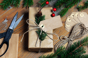 High angle view of Christmas present with labels and strings by pine needles on wooden tableの写真素材 [FYI03744068]
