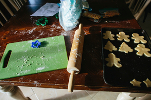 High angle view of Christmas cookies in baking sheet with rolling pin and cutting board on wooden taの写真素材 [FYI03744090]