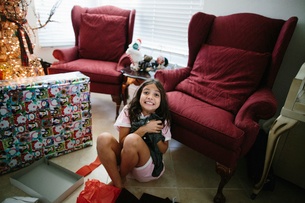 High angle portrait of happy girl holding Christmas present while sitting on floor at homeの写真素材 [FYI03744092]
