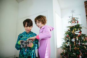 Low angle view of siblings opening Christmas present while standing against wall at homeの写真素材 [FYI03744093]