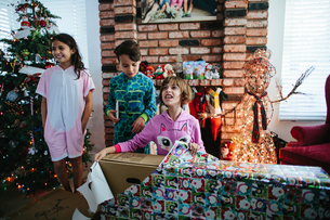 Happy siblings opening Christmas present against brick wall at homeの写真素材 [FYI03744096]