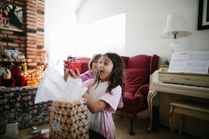 Girl looking at happy sister holding Christmas present in living roomの写真素材 [FYI03744097]
