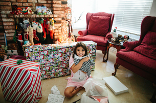 Portrait of happy girl holding Christmas present while sitting on floor at homeの写真素材 [FYI03744099]
