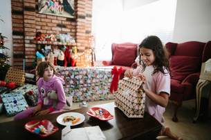 Girl looking at happy sister opening Christmas present on table in living roomの写真素材 [FYI03744101]