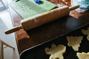 High angle view of rolling pin by Christmas cookies in baking sheet and cutting board on wooden tablの写真素材 [FYI03744102]