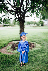 Portrait of boy in graduation gown standing on grassy field at parkの写真素材 [FYI03744456]