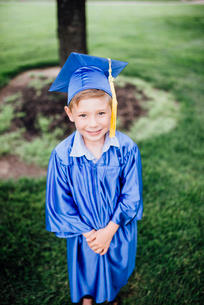 High angle portrait of boy in graduation gown standing on grassy field at parkの写真素材 [FYI03744457]