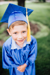 High angle portrait of smiling boy in graduation gown standing on grassy field at parkの写真素材 [FYI03744460]