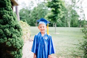 Portrait of happy boy in graduation gown standing at parkの写真素材 [FYI03744461]