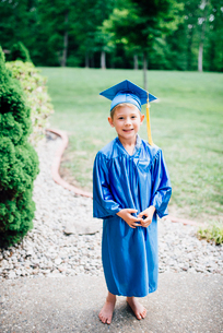 Portrait of boy in graduation gown standing on footpath at parkの写真素材 [FYI03744462]