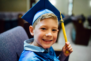 Portrait of happy boy in graduation gown siting on chairの写真素材 [FYI03744463]