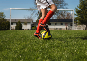 Low section of boy playing with soccer ball on grassy fieldの写真素材 [FYI03744541]