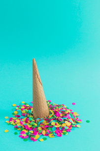 Close-up of cone on colorful confetti depicting fallen ice cream on blue backgroundの写真素材 [FYI03744645]