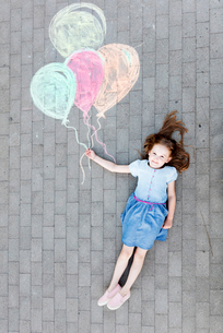 High angle portrait of happy girl lying by colorful balloons drawing on streetの写真素材 [FYI03744844]