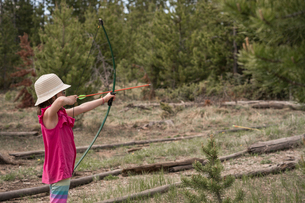 Side view of girl aiming with bow and arrow while standing against trees in forestの写真素材 [FYI03745244]