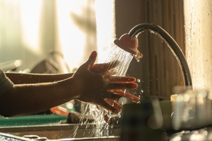 Cropped image of boy washing hands in kitchen sinkの写真素材 [FYI03745380]