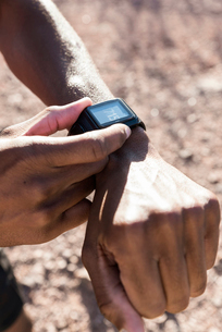 Cropped image of male hiker checking time during sunny dayの写真素材 [FYI03745524]