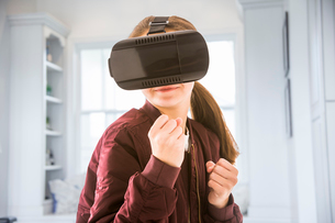 Girl clenching fists while using virtual reality simulator at homeの写真素材 [FYI03745734]