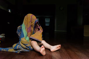 Playful baby boy covering head with towel while sitting on floor at homeの写真素材 [FYI03745800]