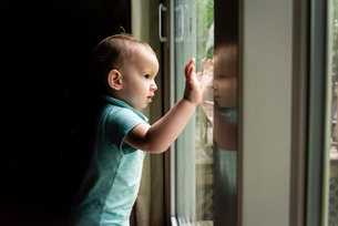 Side view of cute baby boy looking through window while standing in darkroom at homeの写真素材 [FYI03745806]