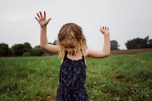 Wet girl with arms raised standing on grassy field against sky at park during rainy seasonの写真素材 [FYI03745907]