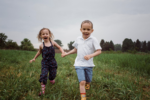 Portrait of happy wet siblings holding hands while running on grassy field against sky at park durinの写真素材 [FYI03745908]