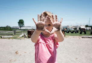 Portrait of girl showing dirty hands while standing on sand against clear sky at playgroundの写真素材 [FYI03745909]