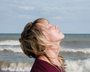 Side view of woman with eyes closed standing by sea against sky during sunny dayの写真素材 [FYI03745917]