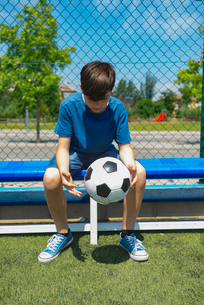 Boy holding soccer ball while sitting on bench by fence at dugoutの写真素材 [FYI03745955]