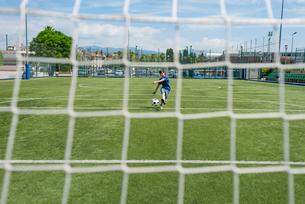 Boy kicking soccer ball against sky seen through netの写真素材 [FYI03745957]