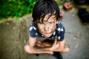 High angle portrait boy with dirty face sitting on footpath at yard during rainy seasonの写真素材 [FYI03746014]