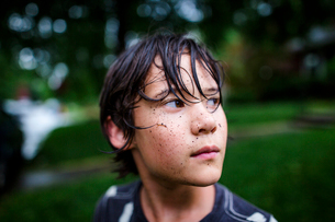 Close-up of thoughtful boy with dirty face standing at yard during rainy seasonの写真素材 [FYI03746016]