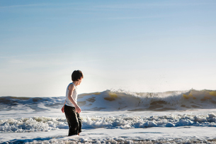 Side view of boy playing with waves while standing in sea against sky during sunsetの写真素材 [FYI03746065]