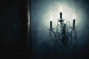 Close-up of illuminated light fixture on wallpaper in darkroomの写真素材 [FYI03746071]