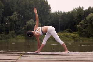 Rear view of woman practicing triangle pose on pier by lake against trees during sunsetの写真素材 [FYI03746562]