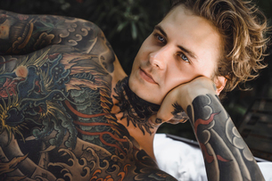 Close-up of thoughtful tattooed man lying on blanket while looking awayの写真素材 [FYI03746586]