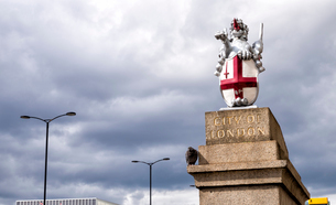 Low angle view of dragon statue with shield and St George's cross against cloudy skyの写真素材 [FYI03746630]