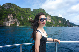 Side view of young woman wearing sunglasses standing by railing on boat in sea against mountainsの写真素材 [FYI03746739]