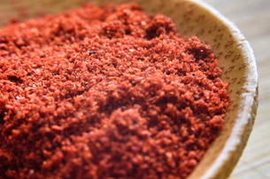 Close-up of chili pepper in wooden spoon on tableの写真素材 [FYI03747353]