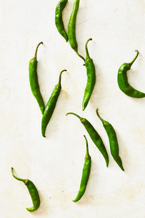 Overhead view of green chili peppers on white tableの写真素材 [FYI03747380]