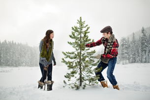Happy couple standing by pine tree on snow covered field against sky in forestの写真素材 [FYI03748257]