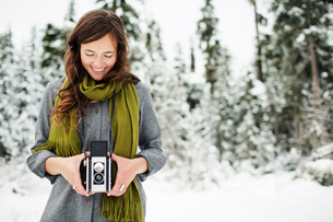 Smiling woman holding camera while standing against snow covered pine trees in forestの写真素材 [FYI03748273]