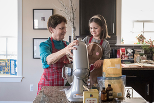 Grandmother and granddaughter making cookie batter using electric mixer in kitchen at homeの写真素材 [FYI03748360]