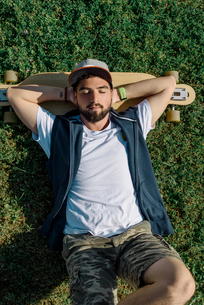 High angle view of handsome man with skateboard lying on grassy field at parkの写真素材 [FYI03748473]