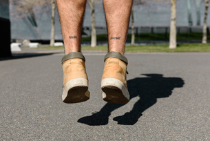Low section of man with tattoo jumping on road during sunny dayの写真素材 [FYI03748475]