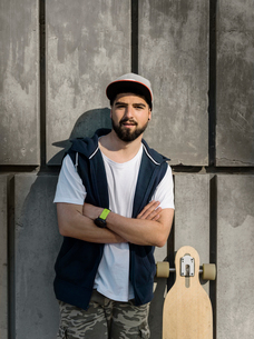 Portrait of confident handsome man with arms crossed standing by skateboard against concrete wallの写真素材 [FYI03748485]