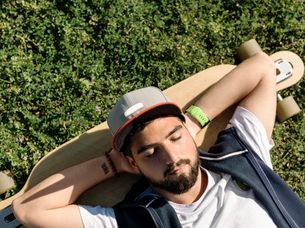 High angle view of handsome man with skateboard lying on grassy field at park during sunny dayの写真素材 [FYI03748505]