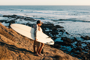 Side view of couple with surfboard looking at sea while standing on rock against sky during sunsetの写真素材 [FYI03748860]