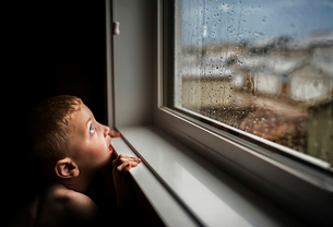 Side view of shirtless boy looking through wet window during rainy season at homeの写真素材 [FYI03748942]