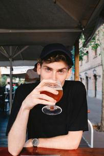 Portrait of handsome man having wine while sitting in restaurantの写真素材 [FYI03749007]